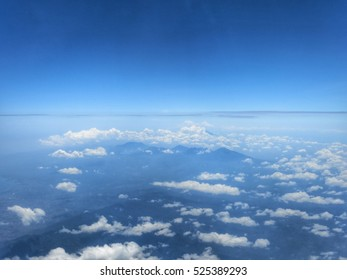 Clear blue sky and white clouds as seen from the airplane window.