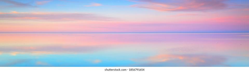 Kleiner blauer Sonnenuntergang mit leuchtenden rosafarbenen Wolken über dem Meer. Symmetrische Spiegelungen auf dem Wasser, natürlicher Spiegel. Atemberaubende Panoramalandschaft. Idyllische Landschaft. Klimawandel, Schönheit in der Natur