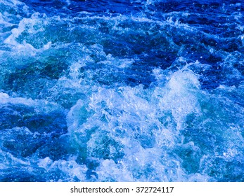 clear blue water glistens, flowing, bubbling and splashing splashing splashes and drops