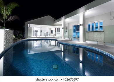 Clear blue water round swimming pool of a modern hotel or house at night with flashing lights