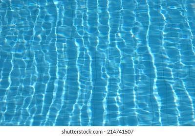 Clear blue water surface of an outdoor swimming pool, showing shiny ripples