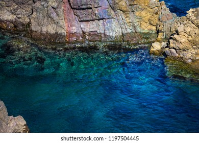 Clear blue waters of the Sea of Japan are pierced with colorful rock formations at Motonosumi Inari Shrine in Yamaguchi, Japan