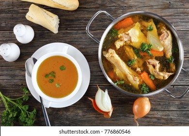 clear Chicken broth with pieces of rooster meat on bone and vegetables in a metal casserole and in a soup cup on dark wooden table, view from above, close-up