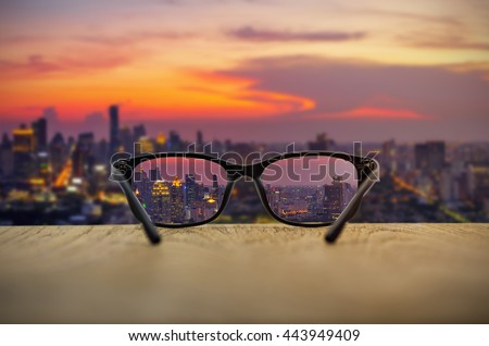 f0098c66f1 Clear cityscape focused in glasses lenses with blurred cityscape background.