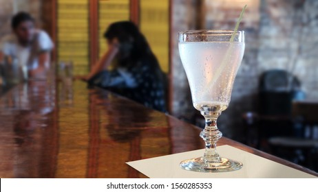 A clear cocktail sitting on a copper bartop during daytime