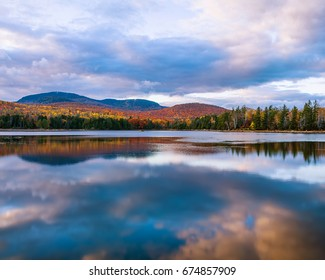 A Clear Colorful Reflection On An Autumn Evening At Loon Lake In The Adirondack Mountains Of New York State, USA