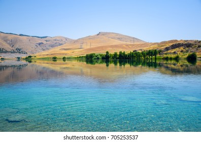 Clear crystal blue water on the Euphrates river near the Ataturk dam with the mountains or hills as a background