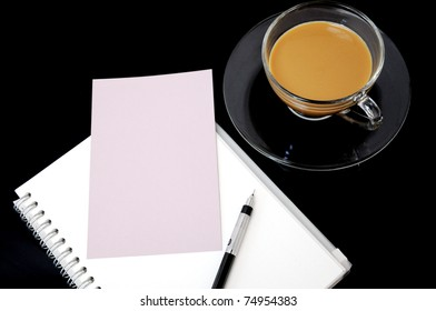 clear cup of coffee on dark background with blank paper