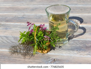 A clear cup of herbal tea and a basket with fresh herbs used in alternative medicine to improve health.
