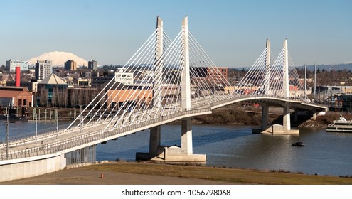 It's a clear day in Portland Oregon at Tilikum Crossing as people traverse the river with Mount St. Helens in the background