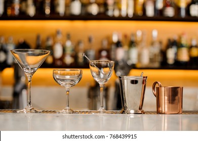 Clear and empty cocktail glasses arranged on the white bar counter against the shelves with bottles