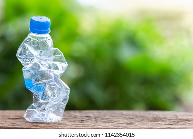 Clear empty plastic bottle on wooden table or counter with green nature light blur background and space for text, design, photo montage or advertising