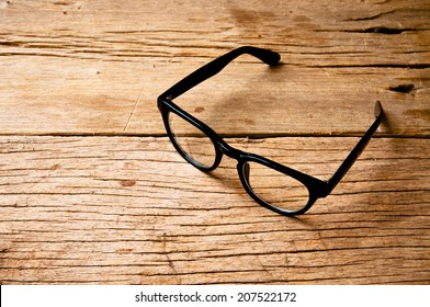 Clear Eyeglasses Glasses with Black Frame Fashion Vintage Style on Wood Desk Background, Rustic Still Life Style.