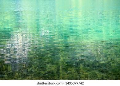 Clear fresh water with small fish and sun refrection. Plitvice Lakes National Park (Nacionalni park Plitvicka jezera). Karlovac County, Croatia.