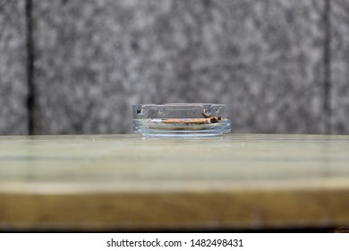 Clear Glass Ashtray with Cigarette Ends on a Wooden Table at a Terrace
