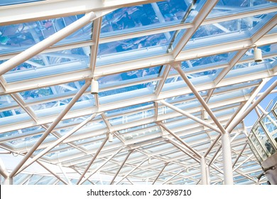 A clear glass atrium roof under blue sky supported by white steel