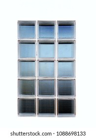 Clear glass blocks wall 3x5 looking through the wall with blue sky and dark shadow on the other side, isolated on white.