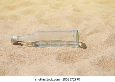 The clear glass bottle on sand at the beach on the day.
