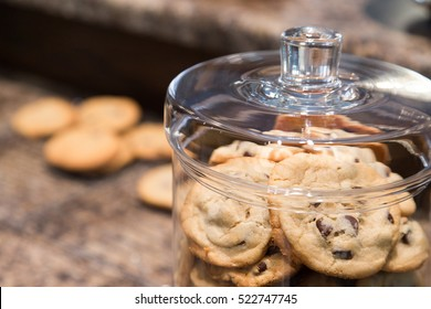 A clear glass cookie jar full of delicious home baked chocolate chip cookies sits on the counter