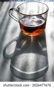 Clear glass cup with tea and its shadow on a table