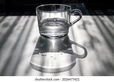 Clear glass cup with water and its shadow on a table