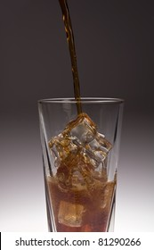 Clear glass with dark soda bring poured over ice against gradient background