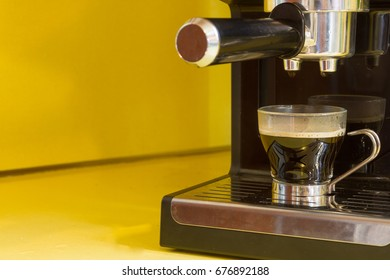 Clear, glass espresso cup filled with foamy, creamy, espresso sitting in a black and chrome espresso maker on yellow kitchen counter. Copy space to the left of photo.
