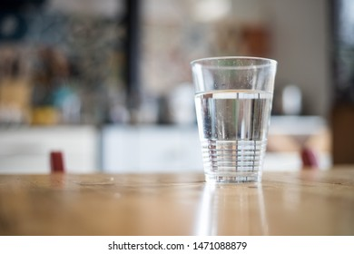 Clear glass of fresh on the wooden kitchen table, cold water