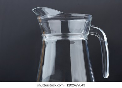 Clear glass jug on black background. Blank glass pitcher on dark background, cropped image. Glass container for water.