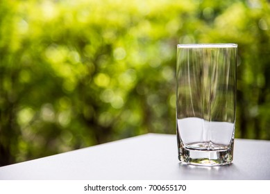 Clear glass on table with green bokeh background