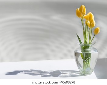 A clear glass vase containing cut yellow tulips and clear glass baubles against a background of gray with water reflections and shadows - created as an art piece.