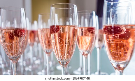 Clear glasses of rose colored champagne invitingly garnished with a vibrant red raspberry