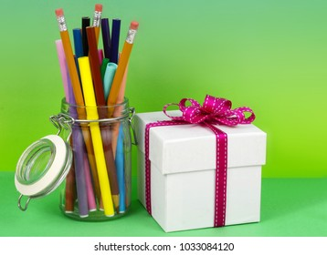 A clear hermetic jar filled with colored markers and pencils with a white gift box tied up with a pink ribbon on a graduated blue green background for administrative professional's day. Copy space.
