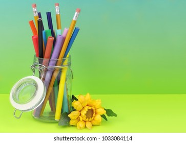 A clear hermetic jar filled with colorful makers and pencils on a graduated blue green blackground with yellow silk flower laying beside. Copy space.