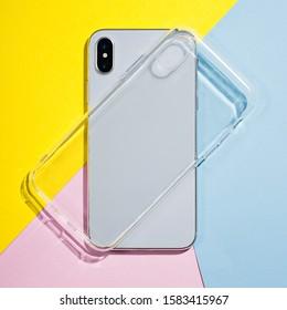 Clear iPhone case mock up. Smart phone on a background of pink, yellow and blue paper, silicone transparent case back view mockup