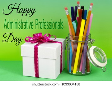 A clear jar filled with colored markers and pencils with a white gift box tied with a pink ribbon on a graduated blue green background for administrative professional's day. Message added