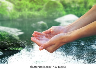 Clear natural water in woman hands on beautiful landscape background.