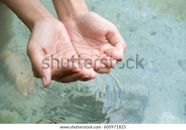 Clear natural water in woman hands.