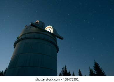 Clear night sky above the lighted open observatory telescope dome, Astronomical observatory of Rozhen, Bulgaria, July 15, 2016.