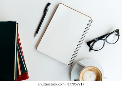 Clear notebook, cup of coffee, glasses, pen and books on white table, flat lay, mock up, point of view.