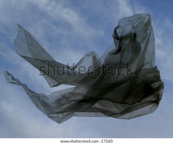 A clear plastic bag floating against a concrete parking lot.
