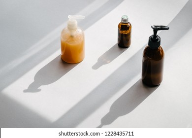 Clear plastic and glass brown bottles with organic cosmetics. Direct light. Beauty blogging minimalism concept