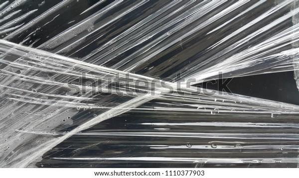 Clear plastic on black wood , texture