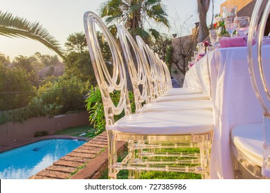 Clear plastic tiffany chairs outdoors glass chairs at table event decor with pool in background