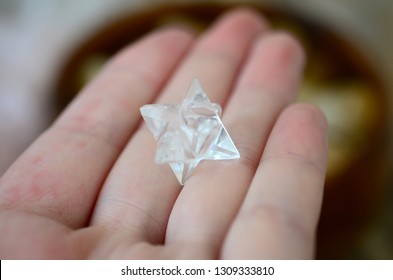 Clear Quartz Merkabas, woman's hand holding crystal. Quartz carving of star, hand holding bright clear quartz. Macro photo in natural lighting.
