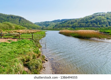 The clear, rippled water of the River Dwyryd flowing across meadows in Snowdonia National Park.