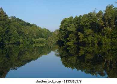 Clear river with a lot of reflection of the surrounding trees
