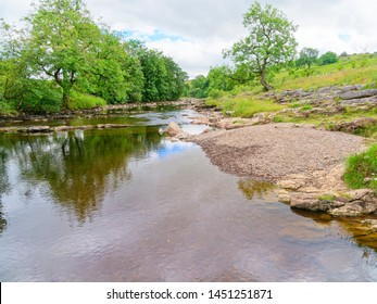 The clear, shallow water of the River Ribble flowing through the Yorkshire countryside near Stainforth.