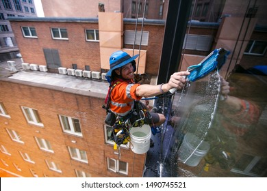 Clear shoot of industrial rope access abseiler face window cleaner wearing full safety harness, helmet fall protection abseiling with twin low stretch ropes conducting cleaning window Sydney CBD