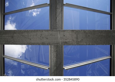 Clear sky above clean glass roof. Close-up of glazed aluminum structure with symmetrical geometric composition. Fragment of industrial, office or warehouse premises. Modern architecture motif.
